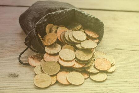 monete antiche: Monete in sacchetto nero in piena luce, stile vintage