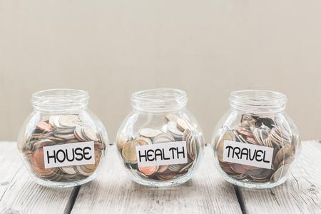 ahorros: Tarro del dinero con las monedas en la mesa de madera, concepto de ahorro Foto de archivo