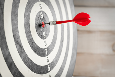 Red dart arrow hitting in the target center of dartboard Stock Photo