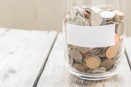 Barattolo dei soldi con le monete sulla tavola di legno, concetto di risparmio