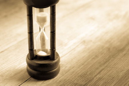 ancient pass: Close-up Hourglass on wood background , antique tone