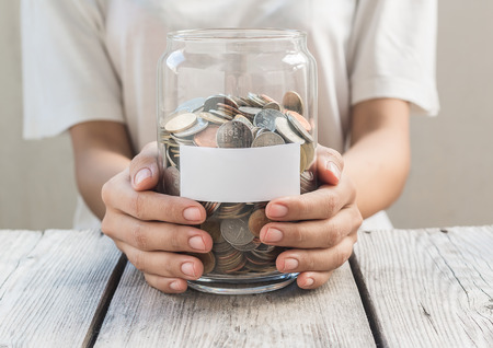 Women hold money jar with coins on wood table , Saving Concept Stock Photo