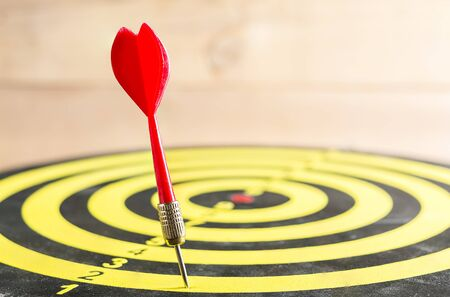 dart on target: Red dart arrow missed in the target center of dartboard