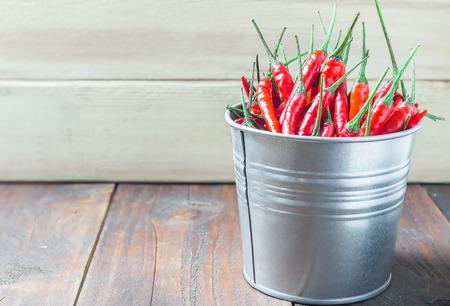 aluminium: red chili peppers in aluminium bucket on wood table