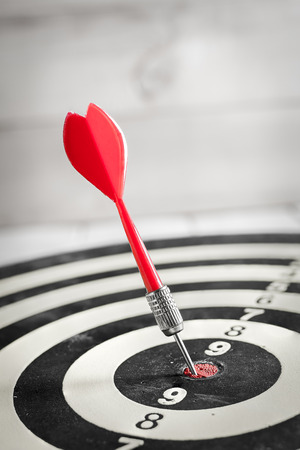 Red dart arrow hitting in the target center of dartboard 免版税图像