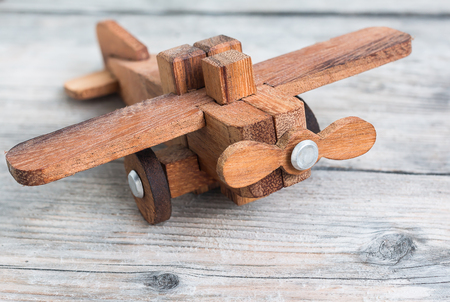 close-up of a wooden toy plane hand carved model on wood background , selective focus