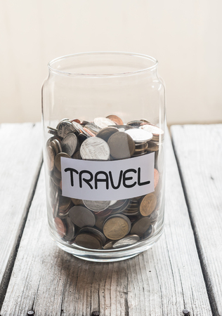 Money jar with coins on wood table , Saving for Travel Concept Standard-Bild