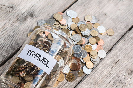money jar: Money jar with coins on wood table , Saving for Travel Concept Stock Photo