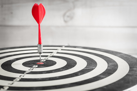 dart on target: Red dart arrow hitting in the target center of dartboard Stock Photo