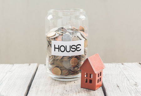 Money jar with coins on wood table , Saving for House Concept