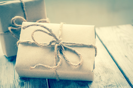 Vintage gift box brown paper wrapped with rope on wood background , vintage tone