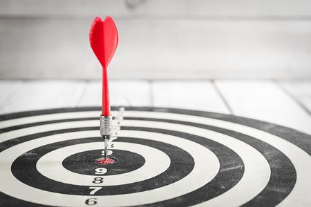DARTS: Red dart arrow hitting in the target center of dartboard Stock Photo