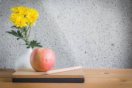 writing desk: Chrysanthemum in White Vase , Notebook , Pencil and Apple on Wood Table , Still Life