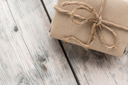 birthday presents: Vintage gift box brown paper wrapped with rope on wood background Stock Photo