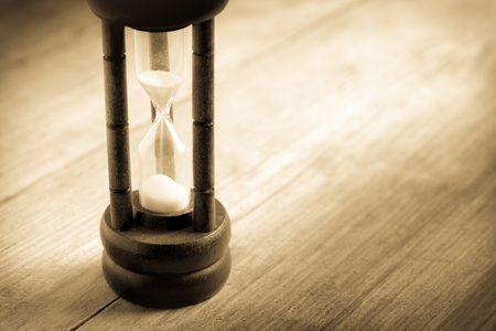 sand timer: Close-up Hourglass on wood background , antique tone