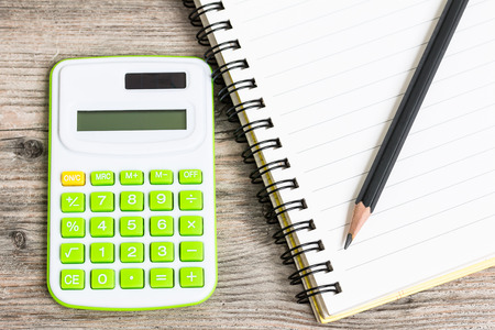 electronic background: Calculator with Notebook and Pencil on Wood Background