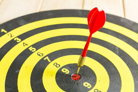financial performance: Red dart arrow hitting in the target center of dartboard Stock Photo