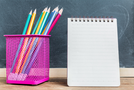 pencil holder: Pencils in pencil holder with notepad on table over black chalkboard background Stock Photo