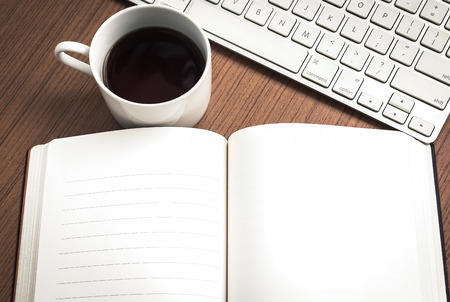 notebook paper background: Empty notebook , keyboard and coffee on wood table   workplace concept