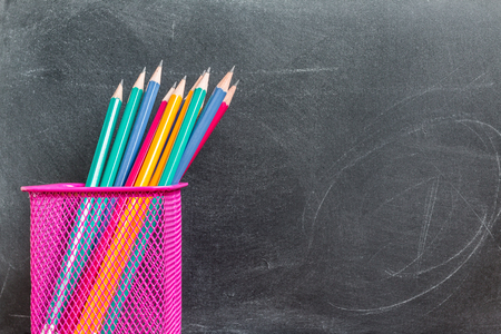 pencil holder: Pencils in pencil holder over black chalkboard background