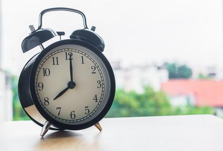reloj: Cosecha de despertador en la mesa de madera al lado del reloj de alarma ventana de muestra 8 en punto