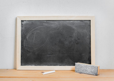 chalk eraser: Blank dirty blackboard , chalk and eraser on wood table over white cement background