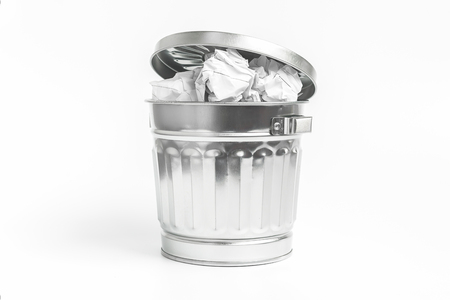 waste basket: Stainless waste basket filled with crumpled paper on white background , waste or frustration concept