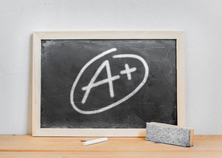 chalk eraser: Grade a plus write on dirty blackboard , chalk and eraser on wood table over white cement background Stock Photo