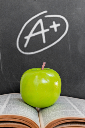 write a letter: Green apple on old  open book over grade a plus on black chalkboard background Stock Photo