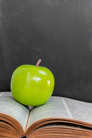 Green Apple On Old Open Book Over Black Chalkboard Background Stock Photo