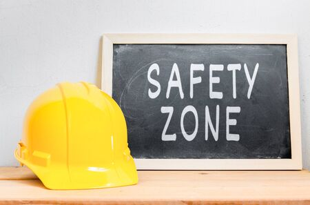 safety wear: Helmet safety with chalkboard  SAFETY ZONE  on wood table , Safety First Concept Stock Photo