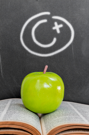 nformation: Green apple on old  open book over grade c plus on black chalkboard background Stock Photo