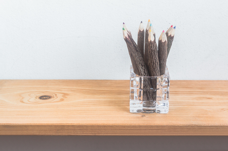 pencil holder: Color pencils in pencil holder from glass on wooden shelf over grunge cement wall