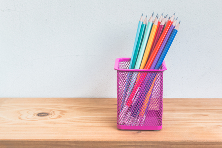 pencil holder: Pencils in pencil holder on wooden shelf over grunge cement wall