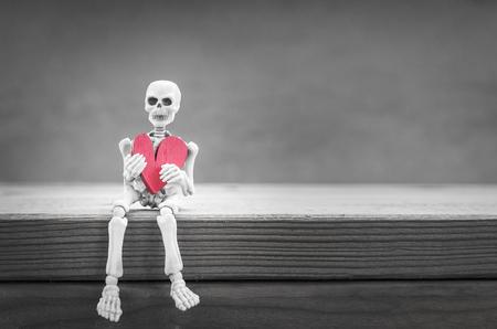 sit shape: Skeleton hold red heart shape sit on wood table