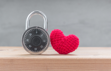 u lock: Red heart shape silk with combination padlock on wood table
