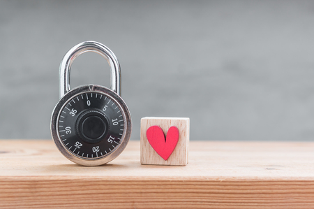 Red heart in wooden cube with combination padlock on wood table Stock Photo