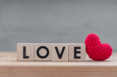 i love you sign: Love in wooden cube with red heart shape silk on wood table