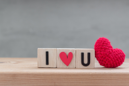 i love you sign: I love you in wooden cube with red heart shape silk on wood table