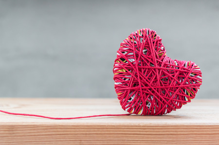Read heart yarn on wood table over grunge cement background