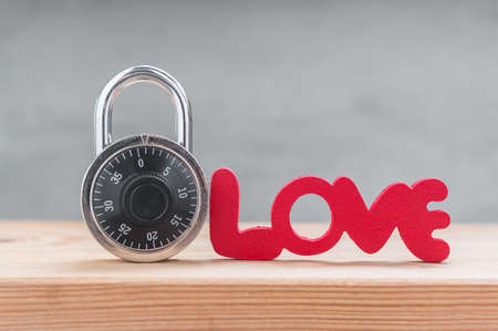 Words Love from wooden with combination padlock on wood table Stock Photo