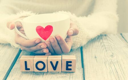 Woman hold cup of love with words Love from wooden cubes - vintage style  , people, relationship and love concept