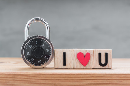 I love you in wooden cube with combination padlock on wood table