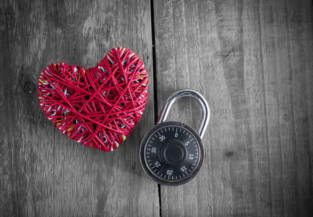 i love you sign: Read heart yarn with combination padlock on grunge wood table Stock Photo