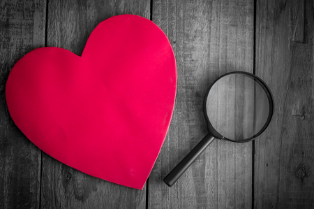 i love you sign: Read heart paper with magnifying glass on grunge wood table Stock Photo