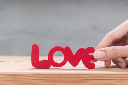 i love you sign: Woman hand hold words Love from wooden on wooden over grung cement background Stock Photo