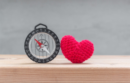 i love you sign: Red heart shape silk with compass on wood table