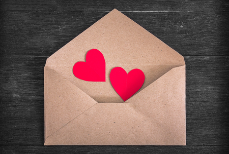 envelope: Brown envelope with red paper hearts on wood background