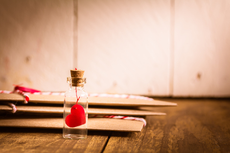 Love heart message in a bottle with envelope on wood table , vintage tone Archivio Fotografico