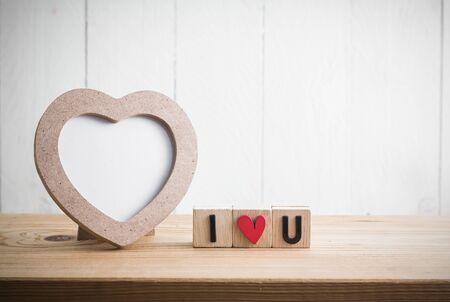 """Herz formte Fotorahmen mit """"i love u"""" in Würfel auf Holztisch"""